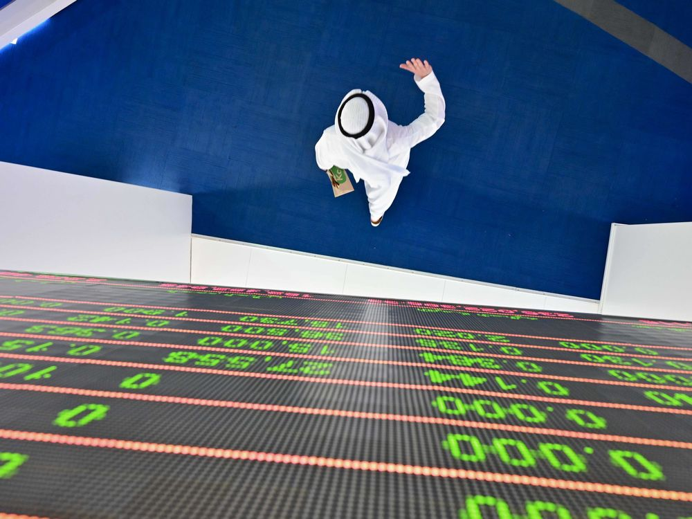 A trader passes under a stock display board at the Dubai Stock Exchange in the United Arab Emirates, on March 8.