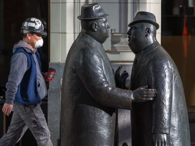 A worker wears a mask as he walks past the well-known statues of two businessman talking in downtown Calgary on Tuesday, March 17, 2020.
