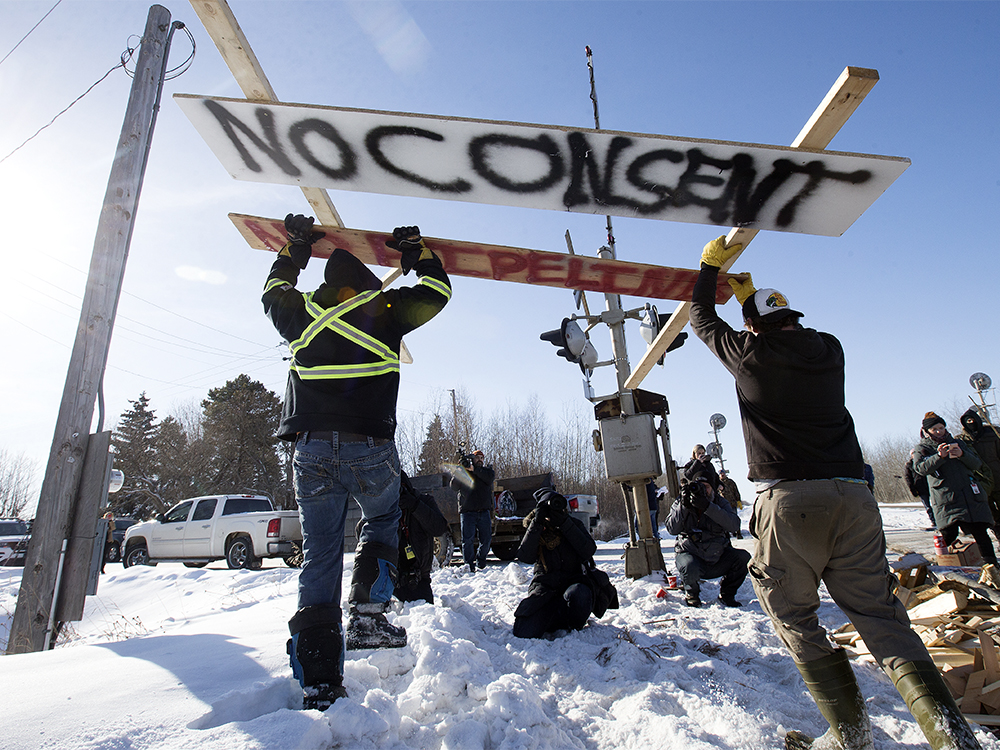 Counter protesters tear down a blockade along the CN rail line near 213 Street and 110 Avenue, in Edmonton Wednesday Feb. 19, 2020. A separate group of protesters had set up the blockade in solidarity with Wet'suwet'en Hereditary Chiefs. Photo by David Bloom