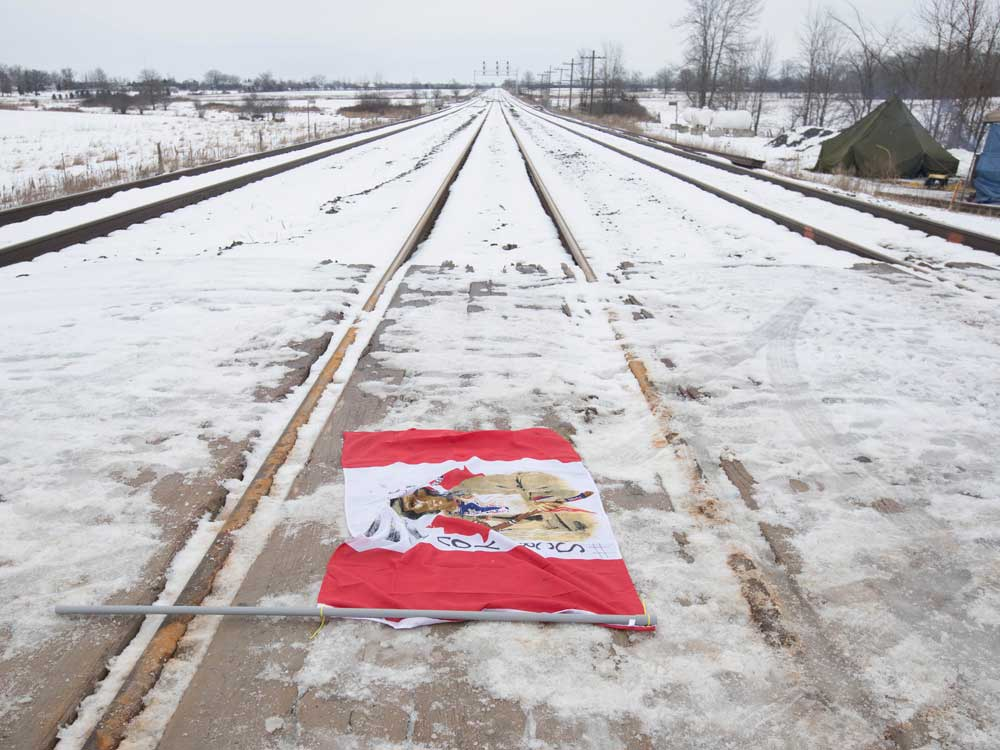 A Canadian flag with Indigenous symbols on it lays across the CN train tracks in Tyendinaga Mohawk Territory, near Belleville, Ont.