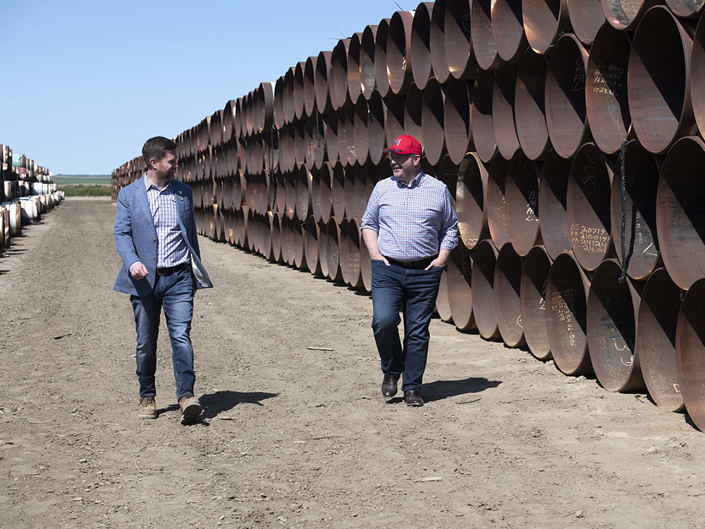 Premier Jason Kenney (right) in Oyen, Alta., surrounded by pipes for the Alberta segment of the Keystone XL pipeline.