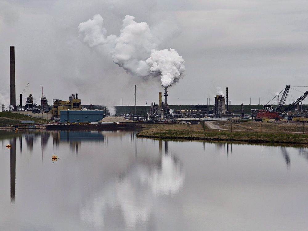 CP-Web. An oil sands extraction facility is reflected in a tailings pond near the city of Fort McMurray, Alberta on Sunday June 1, 2014.