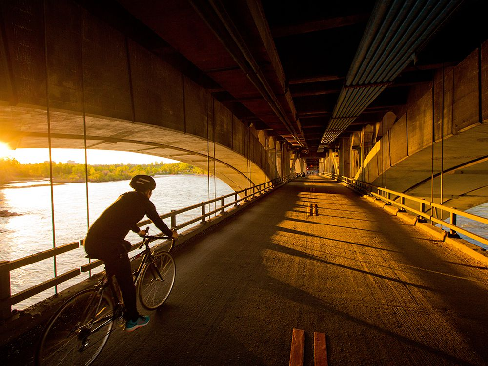 A cyclist crosses the lower deck of the centre street bridge as the setting sun lights up the arches of the 104 year-old bridge on Wednesday, May 27, 2020.