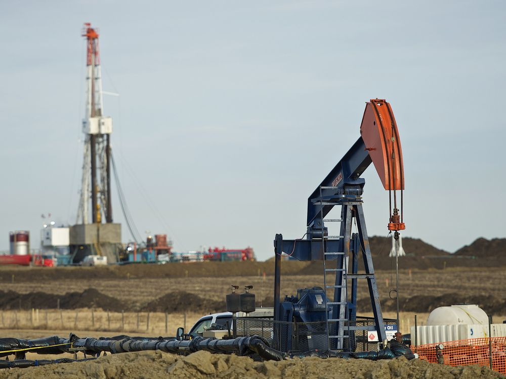 Pumpjack works in the foreground with a drilling rig on a Husky Oil site east of Bruderheim, Alberta.