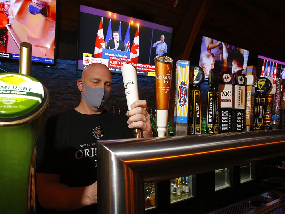 General manager Jason Reeb of The Cat 'n Fiddle Pub pours a beer as Premier Jason Kenney announces new restrictions in Calgary on Tuesday, Dec. 8, 2020.