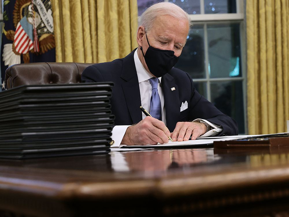 U.S. President Joe Biden signs a series of executive orders in the Oval Office, including an order withdrawing the construction permit for the Keystone XL pipeline, on Jan. 20, 2021.