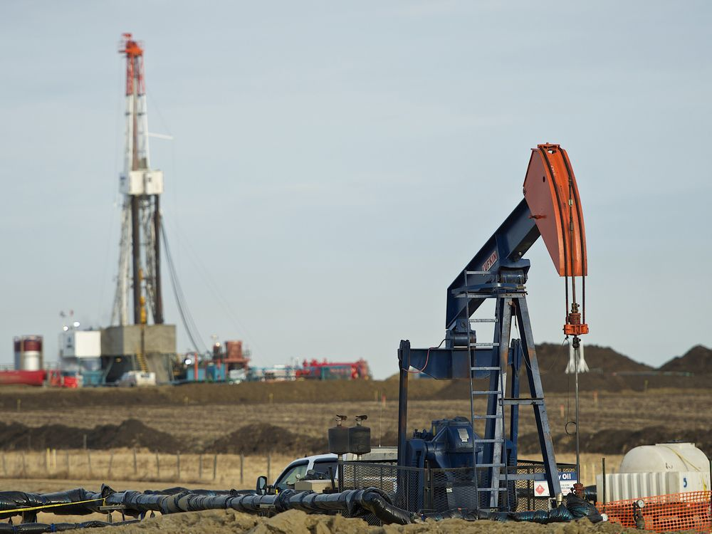 A pumpjack works in the foreground with a drilling rig in the back.