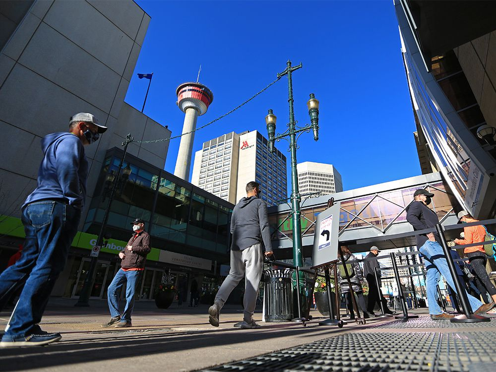 People line up for vaccines outside the Telus Convention Centre in downtown Calgary on Wednesday, April 21, 2021.